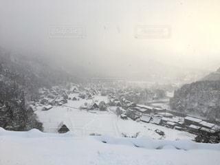 雪に覆われた山の頂上に立っている男の写真・画像素材[1587211]