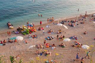 浜辺に座っている人々のグループの写真・画像素材[2387293]