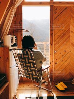 木製のキャビネットの上に座っている人の写真・画像素材[2977181]
