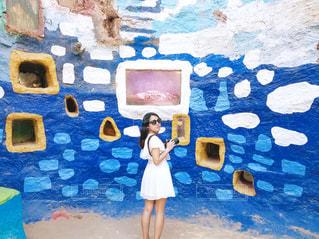 青い壁の前に立っている人の写真・画像素材[997692]