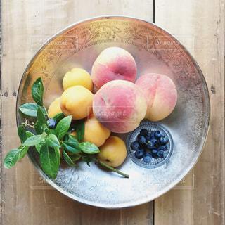 木製のテーブルの上に、シルバーのトレーに乗せたフルーツの写真です。 - No.794017