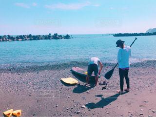 水の体の近くのビーチに立っている人の写真・画像素材[795733]