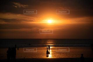 背景の夕日とビーチの上を歩く人々 のグループの写真・画像素材[797673]