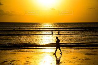 海の横にあるビーチの上を歩く男の写真・画像素材[797677]