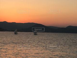 背景の山が付いている水の体に沈む夕日の写真・画像素材[800787]