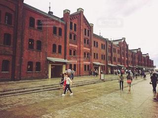 建物の隣に通りを歩く人々 のグループの写真・画像素材[802057]