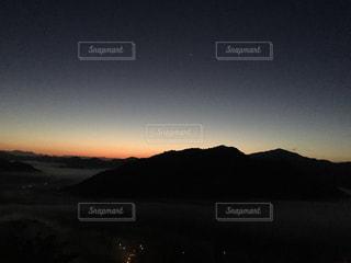 背景の山が付いている水の体に沈む夕日の写真・画像素材[803468]