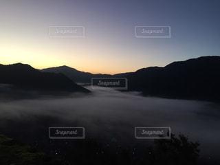 背景の山が付いている水の体に沈む夕日 - No.803474