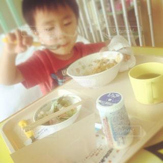食品のプレートをテーブルに座っている少年の写真・画像素材[802690]