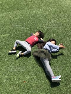 芝生で寝転ぶ子供達の写真・画像素材[1203816]