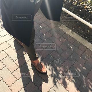 レンガ壁の横の歩道に立っている人の写真・画像素材[971837]