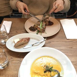 食品のプレートをテーブルに座っている女性の写真・画像素材[992154]