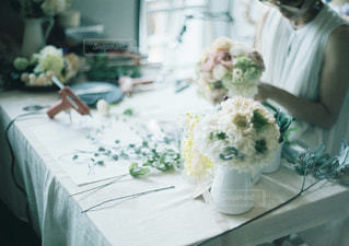 花の花瓶とテーブルに座って人の写真・画像素材[812237]