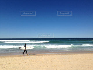 海の横にあるビーチの上を歩く男の写真・画像素材[810816]