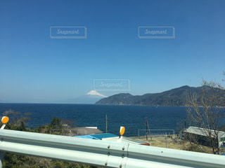 背景の山が付いている水の体の上の橋の写真・画像素材[811397]