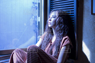 窓辺でくつろぐ素敵な女性の写真・画像素材[1570795]