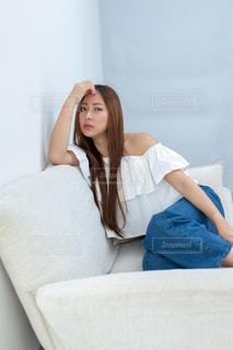 白いソファに座っている女性の写真・画像素材[1781717]