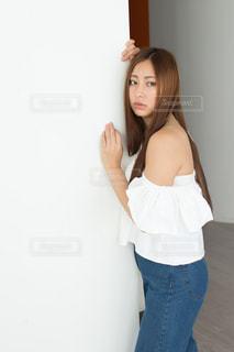 白い壁にもたれる若い女性の写真・画像素材[1781718]