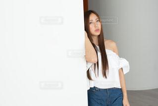白い壁にもたれる若い女性の写真・画像素材[1781719]