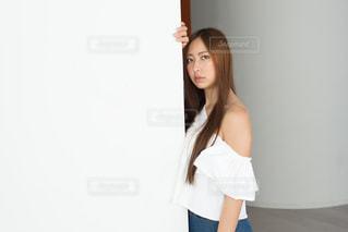 白い壁にもたれる若い女性の写真・画像素材[1781722]