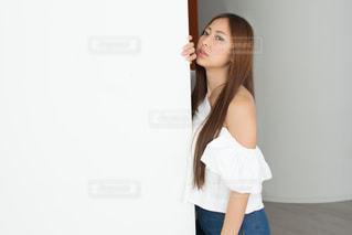 白い壁にもたれる若い女性の写真・画像素材[1781723]