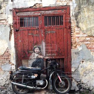 れんが造りの建物の前に停まっている赤いバイクの写真・画像素材[811501]