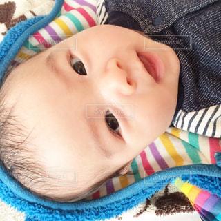 カラフルな毛布の上に横になっている赤ちゃんの写真・画像素材[867408]