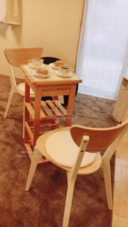 木製のテーブルの前に座っている椅子の写真・画像素材[819769]