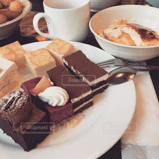 コーヒー カップの横にある皿の上のケーキの写真・画像素材[819983]