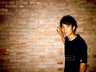 レンガ壁の前に立っている人の写真・画像素材[1032345]