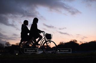 背景の夕日と自転車に乗る人の写真・画像素材[1714824]