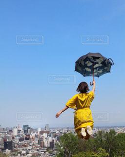 黄色いフリスビーを持ちながら空を飛ぶ男の写真・画像素材[2272792]