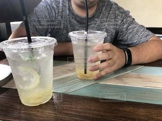 テーブルの上の水のガラスを飲む人の写真・画像素材[2085489]