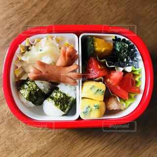 板の上に食べ物の種類でいっぱいの赤いボックスの写真・画像素材[1172582]