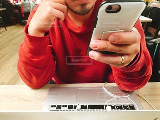 ノート パソコンの前でスマホを持つ手の写真・画像素材[859913]