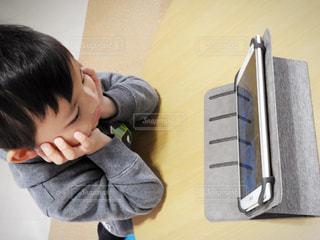 テーブルに座っている小さな男の子の写真・画像素材[881180]