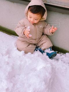 小さな子供は雪の中に座っています。 - No.894058