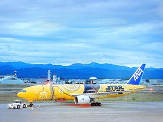 青と黄色の飛行機は空港の滑走路の駐機場に止まっています。の写真・画像素材[1390865]