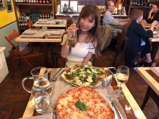 ピザを食べるテーブルに座っている人々 のグループの写真・画像素材[1429679]