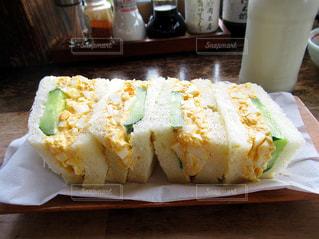 木製のテーブルの上に座ってサンドイッチの写真・画像素材[1668202]