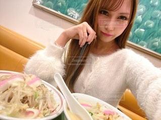 食べ物の皿を持ってテーブルに座っている女性の写真・画像素材[2789920]