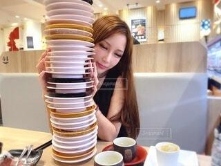 食べ物の皿を持ってテーブルに座っている女性の写真・画像素材[3773355]