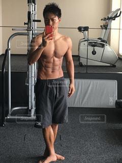 カメラにポーズ鏡の前に立っている若い男 - No.1218762