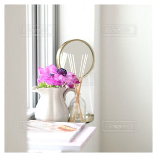 紫の花と白い花瓶のある窓辺の写真・画像素材[980319]