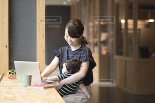 パソコンで作業するママと赤ちゃんの写真・画像素材[1439577]