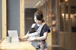 パソコンで作業するママと赤ちゃんの写真・画像素材[1439612]