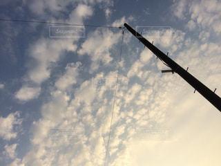 曇りの青い空を飛んでいる飛行機の写真・画像素材[1134138]