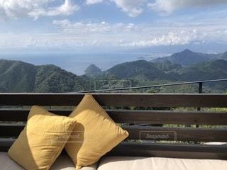 背景の山が付いているベンチの写真・画像素材[1487393]