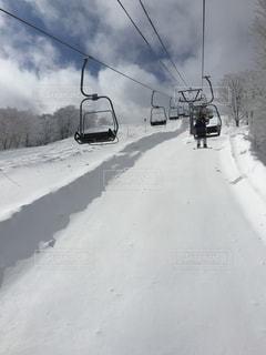雪に覆われた斜面をスキーに乗っている人のグループ - No.841546