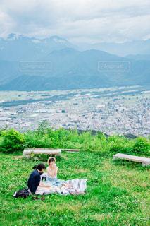 フィールドの背景の山に座っている人々 のグループ - No.843675